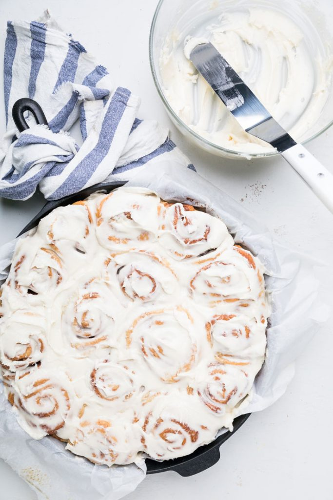 vegan cinnamon rolls and frosting in a cast iron skillet