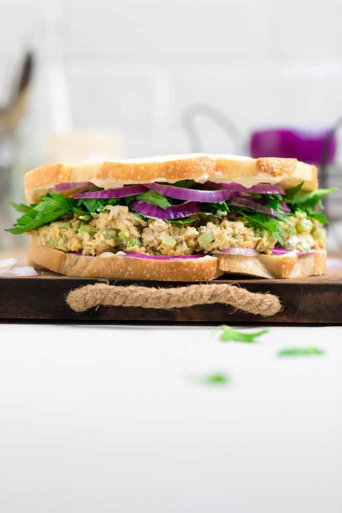 vegan chicken salad sandwich with lettuce and red onions on a cutting board
