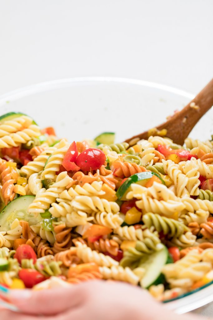 Italian vegan pasta salad in a clear bowl with a wooden spoon