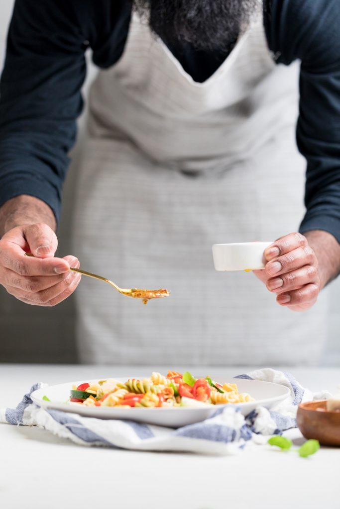 man spooning dressing over vegan pasta salad