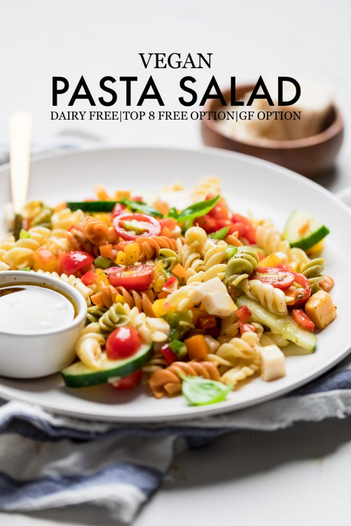 vegan pasta salad in a white bowl with text written over that says: vegan pasta salad dairy free top 8 free option gf option