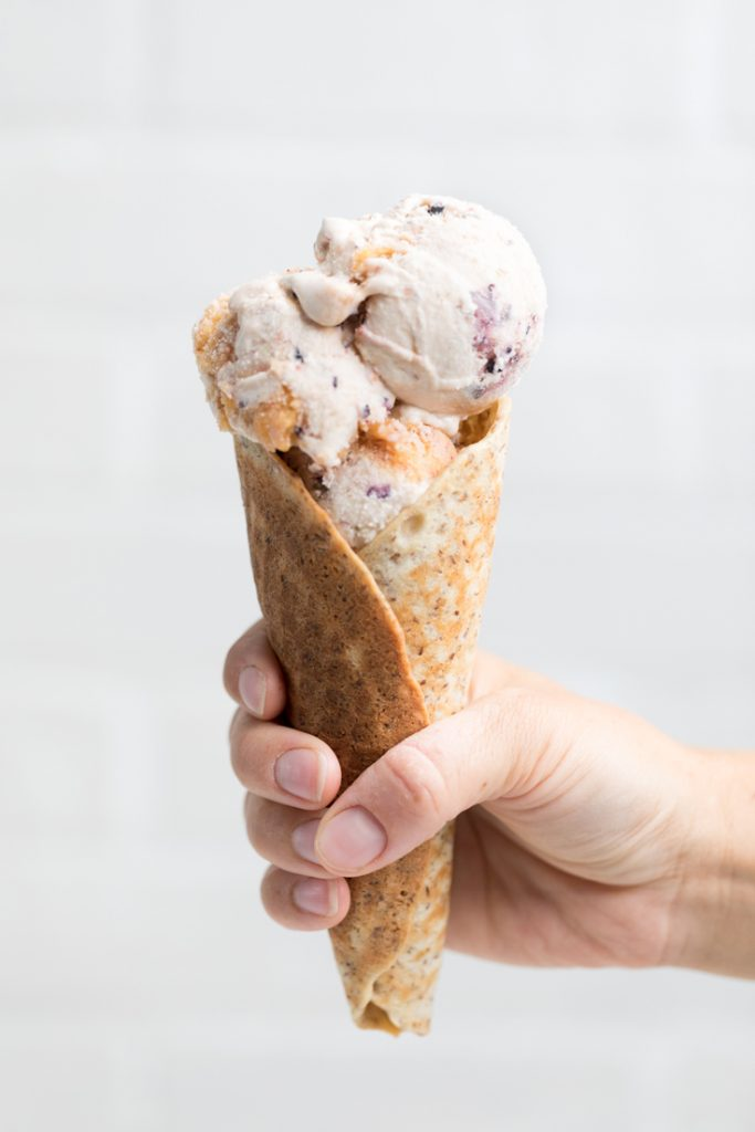 person's hand holding vegan peach blueberry ice cream in a cone
