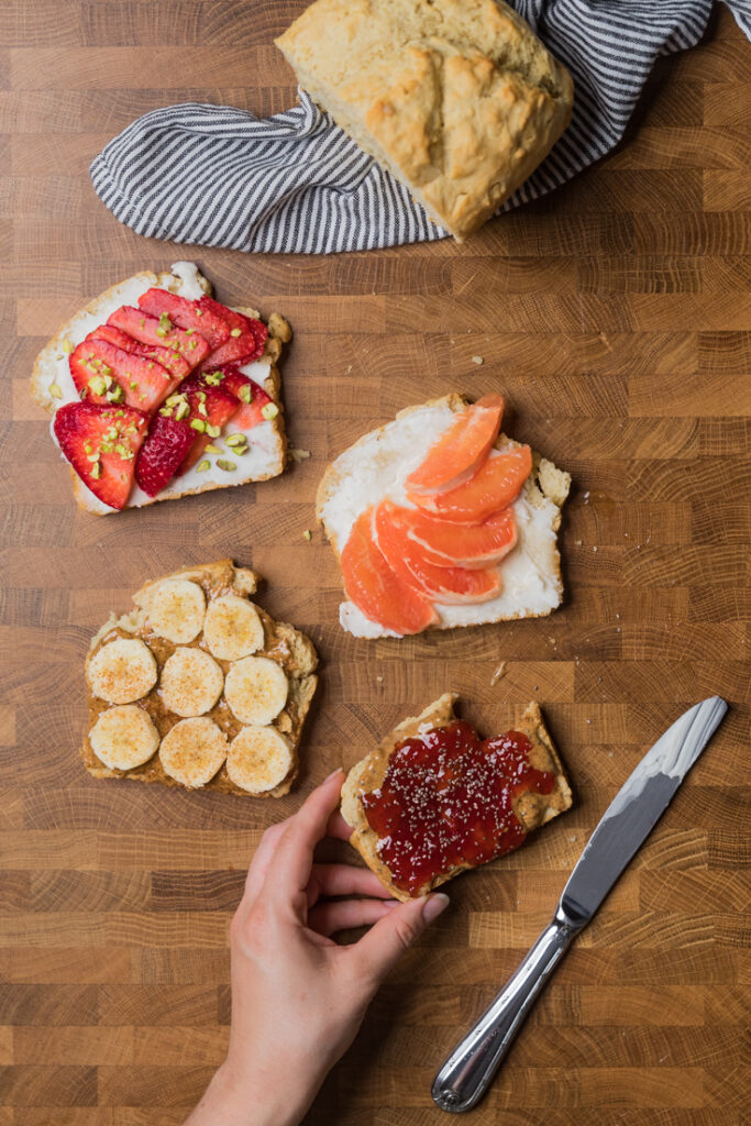 4 slices of yeast free vegan bread with toppings. One is vegan cream cheese with slice strawberries and chopped pistachios. One is vegan cream cheese with sliced grapefruit and agave. One is almond butter, sliced bananas and cinnamon. And one is almond butter, strawberry jam and chia seeds.