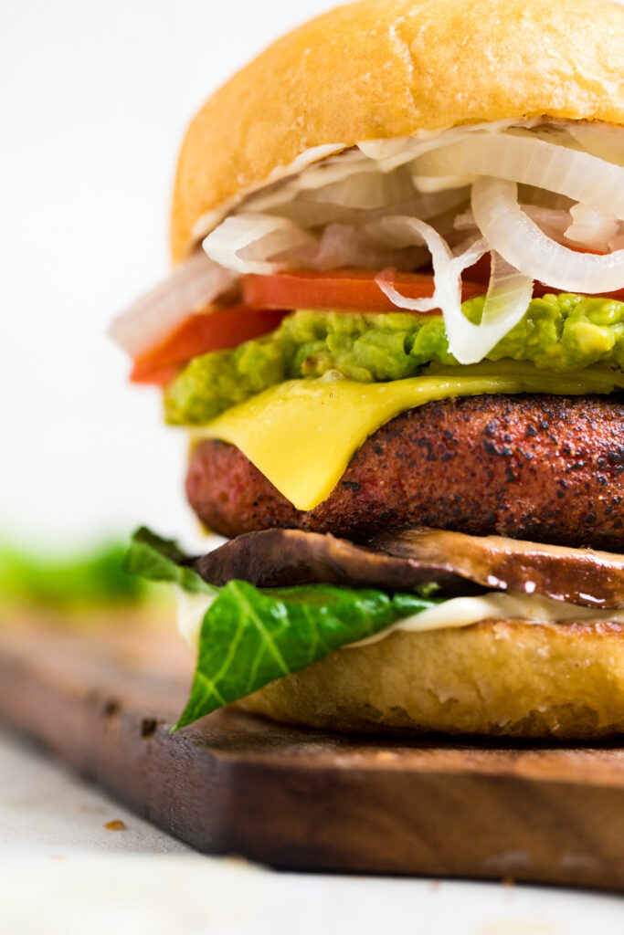 close up of high protein vegan burger on a cutting board to the right of the image