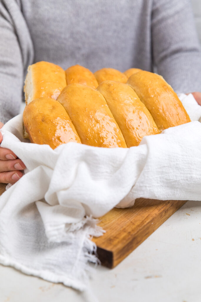 Hands holding vegan hot dog buns in a towel lined bowl