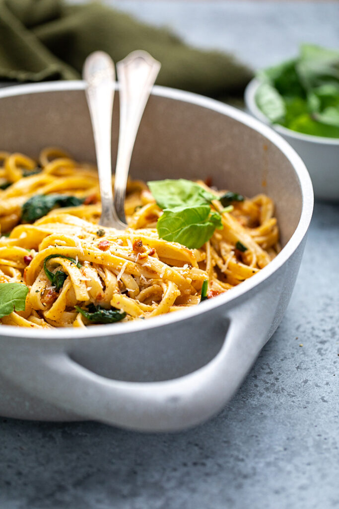 close shot of vegan spinach and sun dried tomato pasta in a skillet