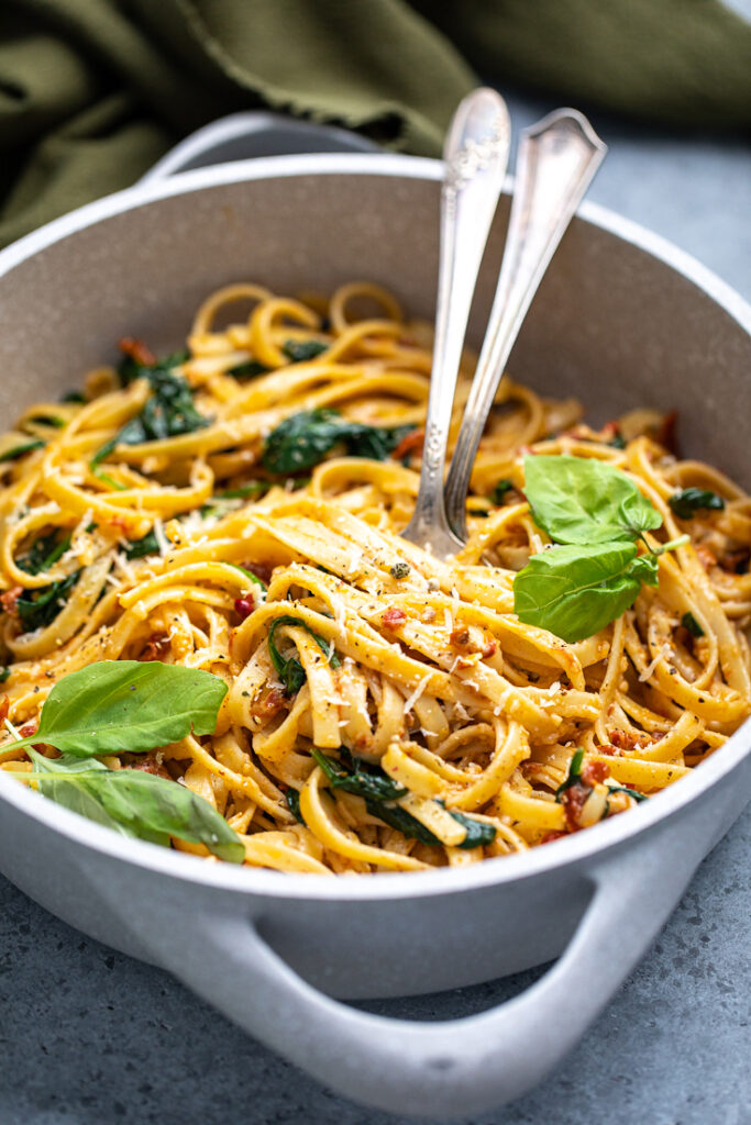 overheard view of vegan spinach and sun dried tomato pasta in a skillet