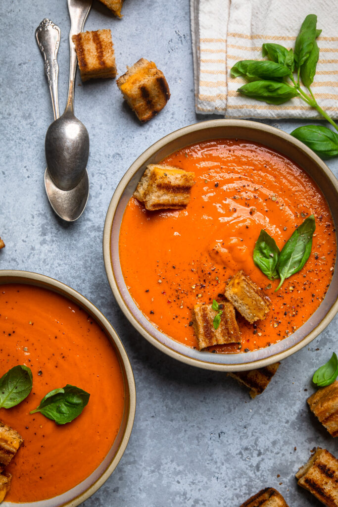 Two bowls of tomato soup with cubes of grilled cheese in the bowl with basil leaves
