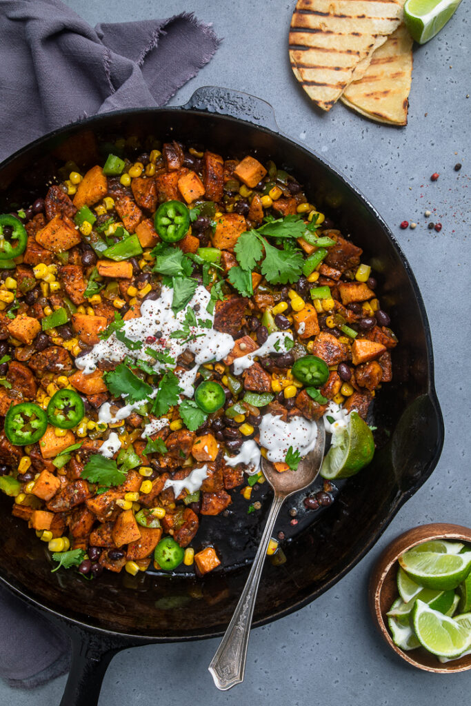 Vegan Mexican Sweet Potato Breakfast Hash zoomed out with a bowl of limes slices in the bottom right